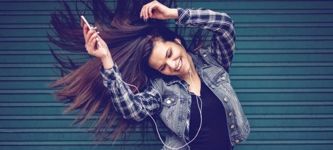woman dancing with earbuds in