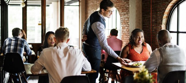 server serving food to couple at restaurant