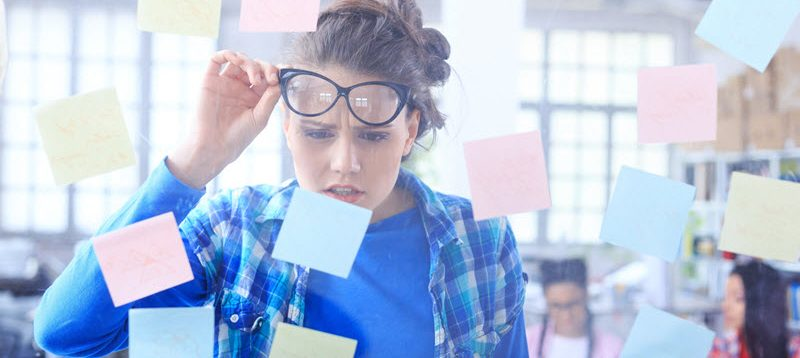 woman looking confused while reading sticky note