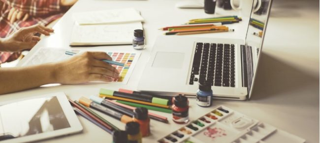 woman with colored pencils and paints designing a logo