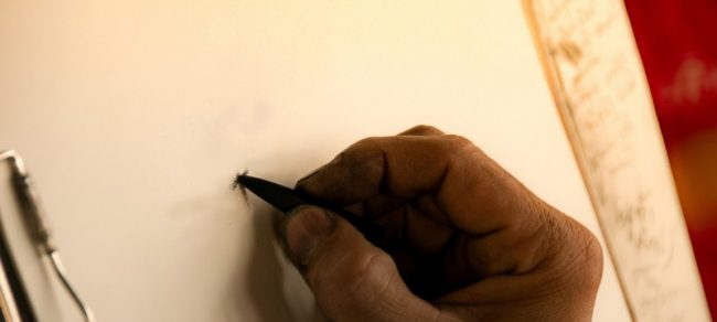 Close up of hand holding pencil on paper