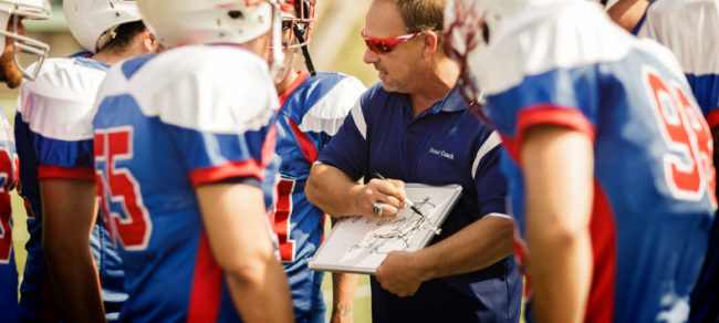 Football coach going over play to football players.