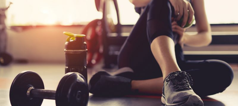 woman on floor exercising with dumbbell