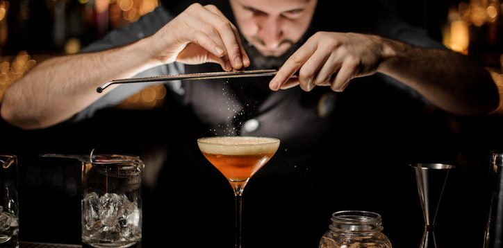 Professional bartender adding to a cocktail in the glass with a whipped cream a grated nutmeg