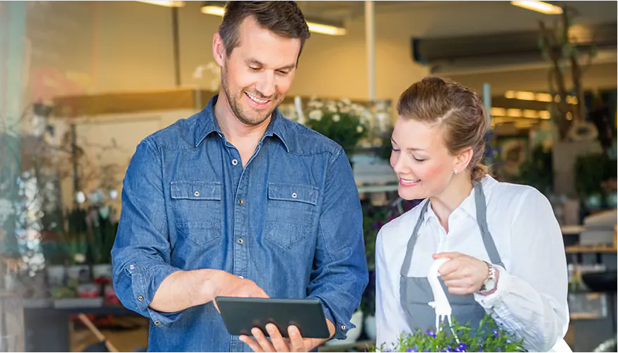 Male and female Entrepeneur searching for research about small business loans on their tablet